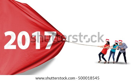 Group of Asian people wearing christmas hat and pulling a red banner with number 2017, isolated on white background
