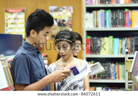Group of asian students looking for books in the library - stock photo