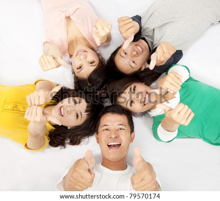 group of asian young people lying together with thumb up - stock photo