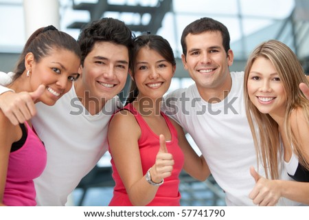 Group of athletic people at the gym with thumbs up - stock photo