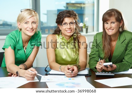 Group of attractive businesswomen sitting at meeting room, discussing financial charts on table, smiling. - stock photo
