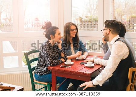 Group of attractive young friends having fun in a cafe bar in a sunny day - stock photo