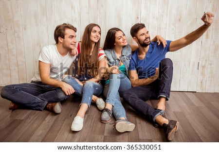 Group of attractive young people sitting on the floor, doing self, smiling, looking at camera - stock photo