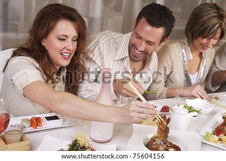 Group of attractive young professional people eating at upscale restaaurant - stock photo