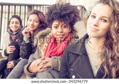 Group of attractive young women of different ethnics sitting on stairs and smiling at camera - Four students sitting outside university - Best friends spending time together - stock photo