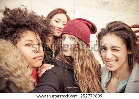 Group of attractive young women of different ethnics taking a selfie - Four students smiling at camera - Best friends spending time together - stock photo