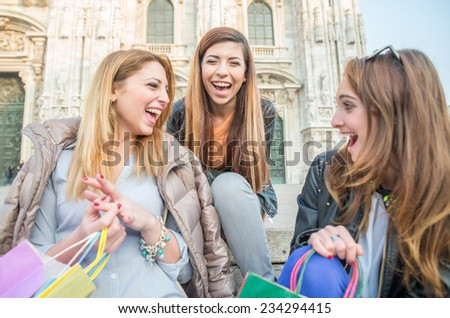 Group of attractive young women sitting on stairs and smiling and laughing - Three students sitting outside university - Best friends spending time together - stock photo