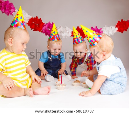 Group of babies looking at cupcakes with birthday candles - stock photo