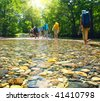 Group of backpackers fording cold river - stock photo