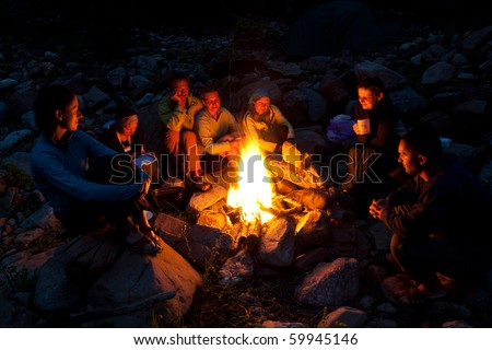 Group of backpackers relaxing near campfire after a hard day, tourist background. - stock photo