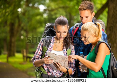 Group of  backpackers stopped on hiking trail and reading map - stock photo