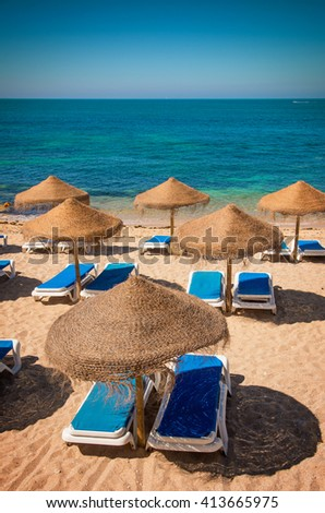 Group of beach sun-shades and deck-chairs with blue mattresses  - stock photo
