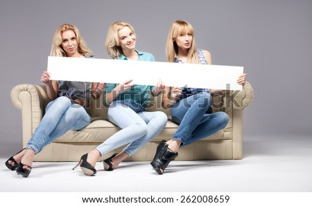 Group of beautiful blonde woman holding empty board, smiling and looking at camera. Studio shot. - stock photo