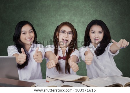 Group of beautiful female students with long hair, showing thumbs up on the camera in the classroom - stock photo