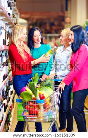 group of beautiful girls choosing wine in supermarket - stock photo
