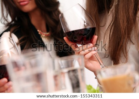 Group of beautiful girls enjoying red wine at home - stock photo