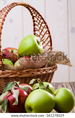 Group of beautiful raw ripe juicy red and green apples with leaves on stalks near wicker basket full of apples decorated with burlap on wooden table on white wall background, vertical photo - stock photo