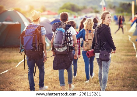 Group of beautiful teens arriving at summer festival - stock photo