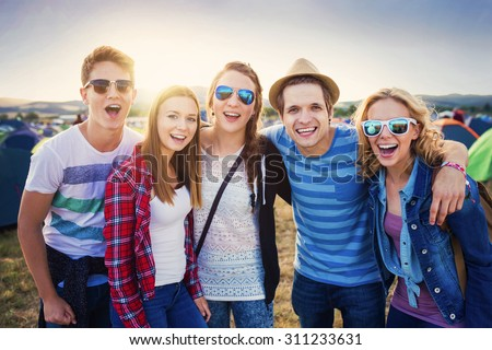 Group of beautiful teens at summer festival. Young teens at summer music festival. Funny group of young girls and boys at music festival. Happy teen at summer festival. - stock photo