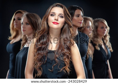 Group of beautiful women. Attractive young woman in black dress with long hair looking at camera and her friends standing in front her back against black background. - stock photo