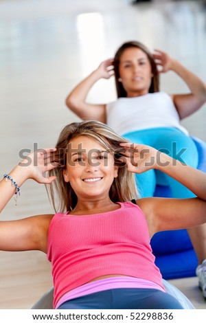 Group of beautiful women in a pilates class at the gym - stock photo