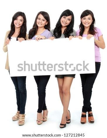 Group of beautiful women smiling with blank board - stock photo