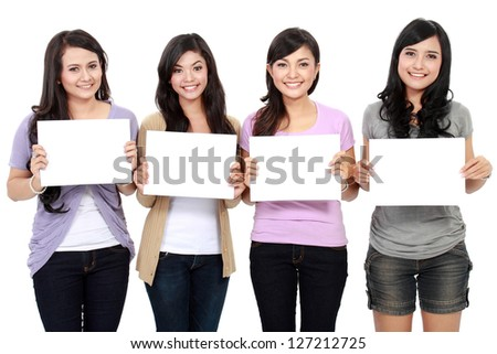 Group of beautiful women smiling with blank paper on their chest