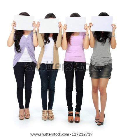 Group of beautiful women with blank paper covering their face - stock photo