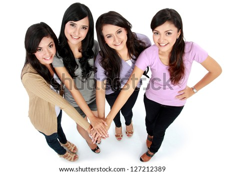 Group of beautiful women with their hands together isolated over a white background