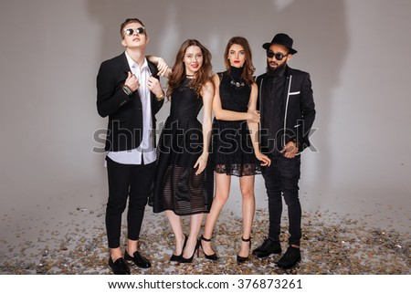 Group of beautiful young people in black suits and dresses standing over white background - stock photo