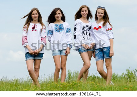 group of 4 beautiful young women girlfriends in folk embroidery dresses having fun happy smiling standing in green field & looking at camera on blue sky summer outdoors background portrait image - stock photo