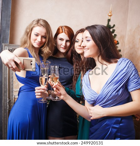 Group of beautiful young women with glasses of champagne making photo on smartphone - stock photo