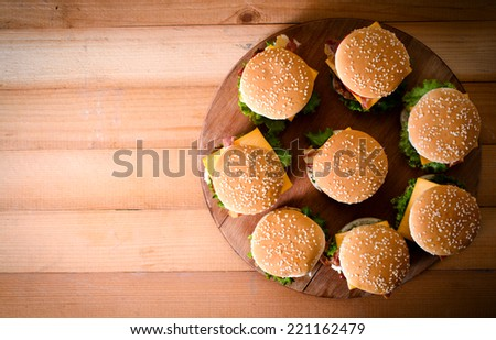 Group of beef burgers on the wooden background,from above and selective focus.Blank space on the left side - stock photo