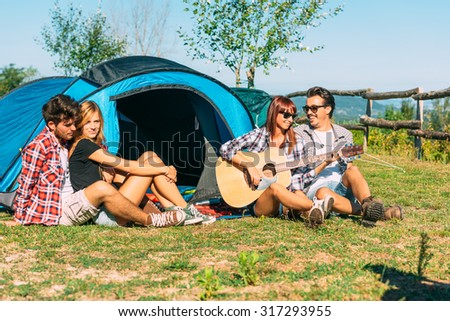 Group of best friends singing and having fun camping together - Concept of carefree youth and freedom outdoors in the nature