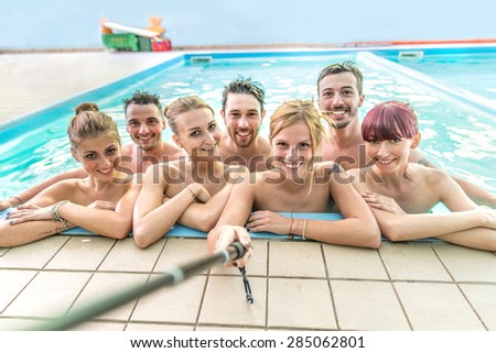 Group of best friends taking selfie with stick in a swimming pool - Young and attractive people having fun and partying on summer vacation - Girl holding selfie stick and photographing her friends - stock photo