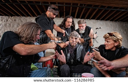 Group of bikers in leather hold up sitting man