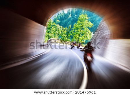 Group of bikers touring along European mountains, riding in tunnel, extreme lifestyle, slow motion, traveling and tourism concept - stock photo