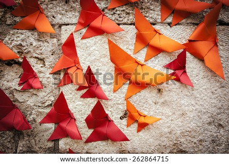Group of birds Origami orange and red on a wall.