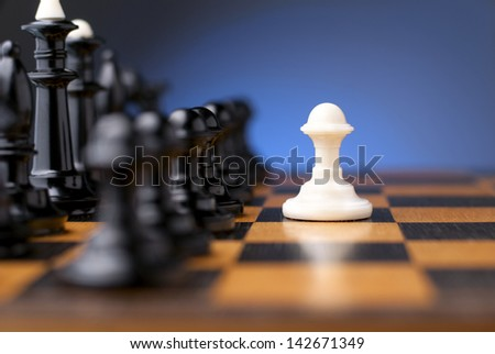 group of black chess on a chessboard and a white pawn in front of them - stock photo