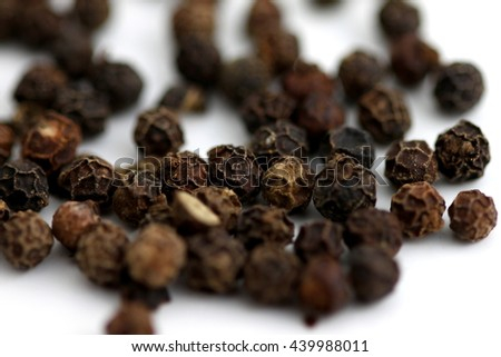 Group of black pepper corns on white background. - stock photo