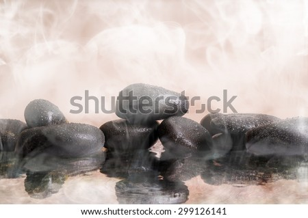 Group of black stones in the warm water, steam background. Spa, sauna, relaxation, meditation and health concept. - stock photo