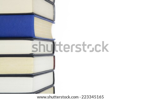 Group of books stacked high and one book standing out from others with spine showing. - stock photo