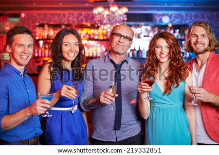Group of boozing people with drinks looking at camera at party - stock photo