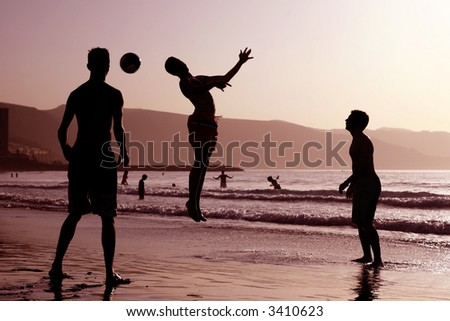 Group of boys playing football on the beach - stock photo