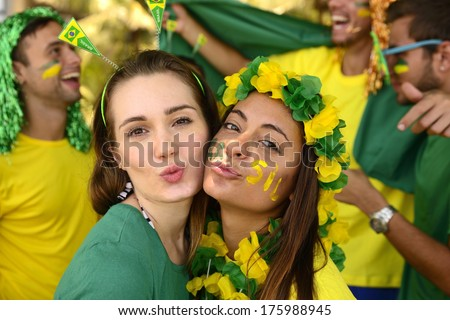 Group of Brazilian girls soccer fans commemorating victory posing kissing. - stock photo