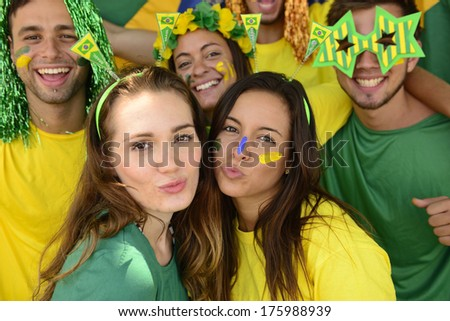 Group of Brazilian soccer fans celebrating victory kissing. - stock photo