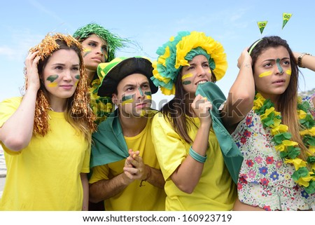 Group of Brazilian soccer fans concerned with the performance of the national team. - stock photo