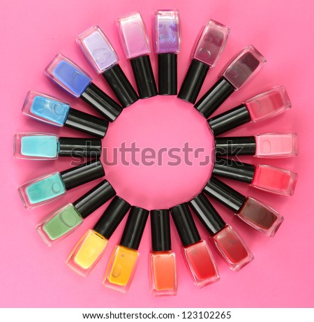 Group of bright nail polishes, on pink background - stock photo