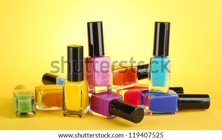 Group of bright nail polishes, on yellow background - stock photo
