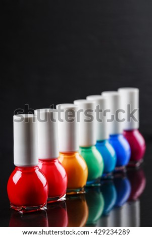 Group of bright nail polishes sorted like a rainbow. Bottles with water drops are standing in a row on black stone background with reflection. Beauty concept. - stock photo